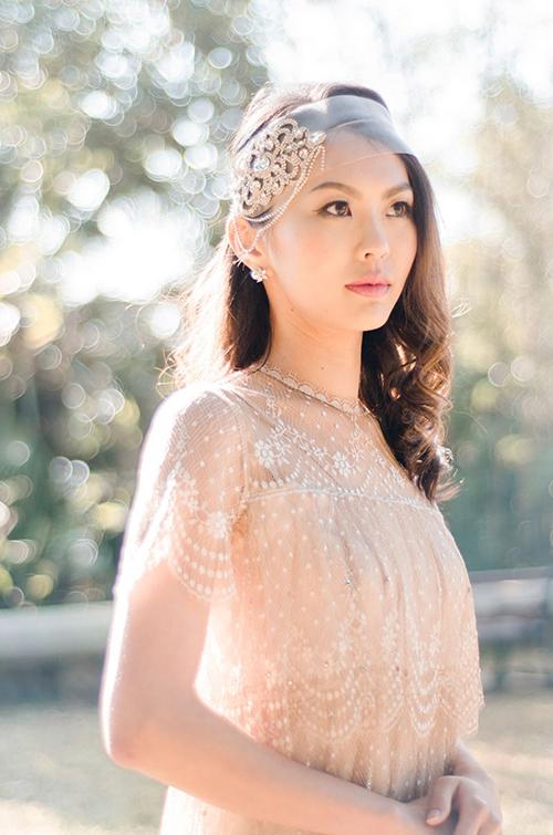 Với mái tóc xoăn nhẹ bồng bềnh, cô dâu diện bờm vải đính đá và ngọc trai để thêm phần nổi bật.