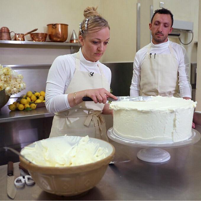 Đầu bếp Claire Ptak phết kem bơ xung quanh chiếc bánh. Cô Claire đã thực hiện chiếc bánh này cùng với 6 đầu bếp trong suốt 5 ngày liên tiếp tại căn bếp của Cung điện Buckingham. Ảnh:Instagram Kensington Royal.
