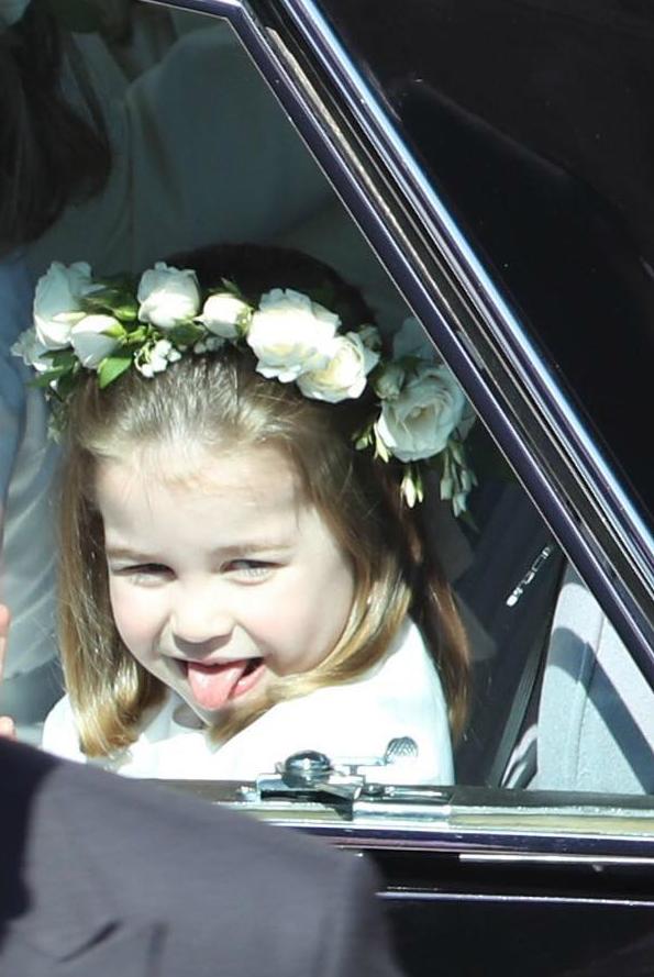 Công chúa nhỏ lè lưỡi trêu chọc ai đóbên ngoàikhi ngồi trong ôtô tới đám cưới.