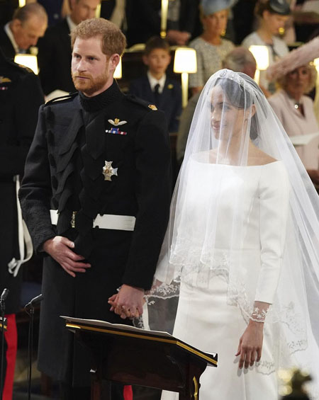 Harry nắm chặt tay Meghan khi làm lễ. Ảnh: AFP.