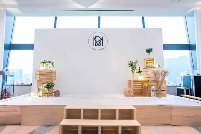 Không gian tiệc cưới tuân theo chủ đề mộc mạc với background màu trắng vàkhối hộp gỗ xếp chồng lên nhau. Những tán lá màu xanh góp phần tô điểm thêm nét lãng mạn cho không gian.