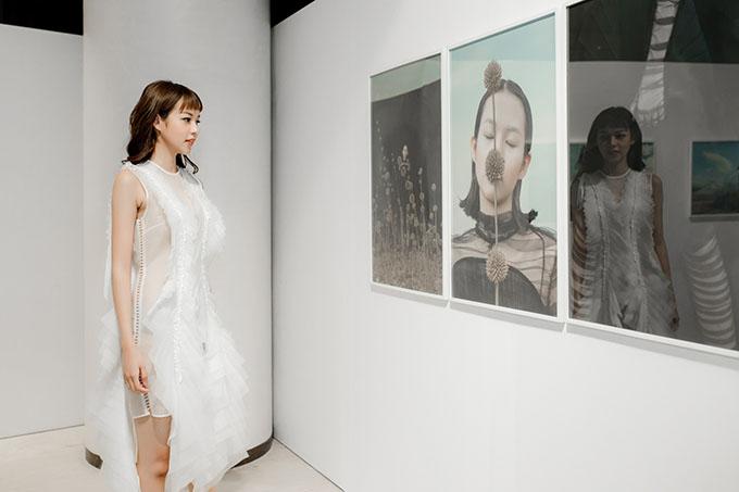 Nữ người mẫu ngắm tác phẩm nhiếp ảnh có tênThe Stranger chụp chính cô được trưng bày tại triển lãm.