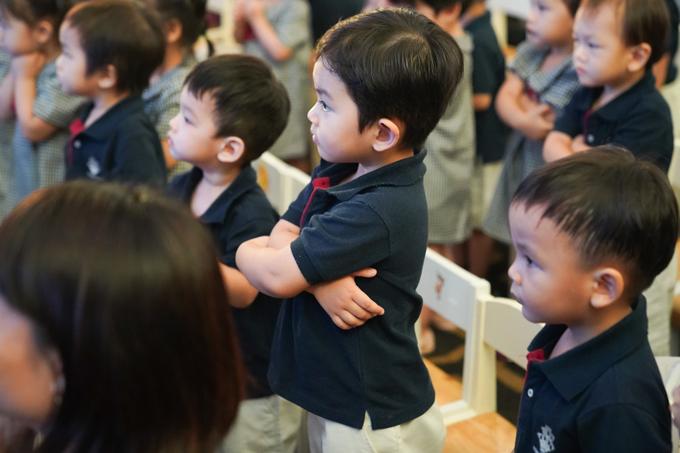 Cậu nhóc ngoan ngoãn làm theo sự hướng dẫn của thầy cô, khoanh tay chào mọi người.