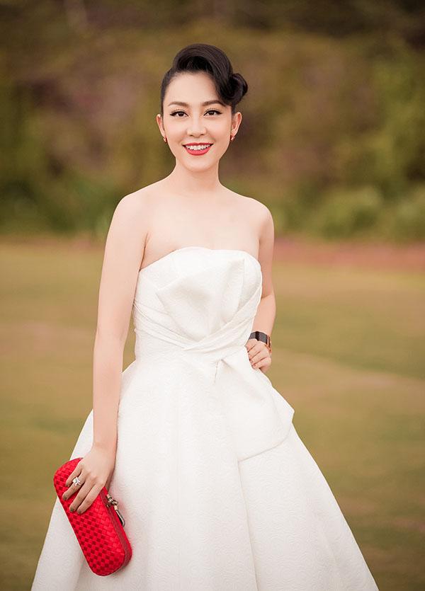 Diễn viên múa Linh Nga trang điểm và làm tóc quý phái theo phong cách cổ điển khi diện váy xoè xoắn eo trên chất liệu vải trắng thanh nhã.