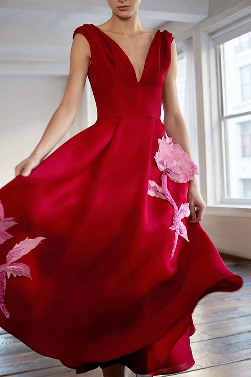 3. Váy có hoa:Carolina Herrera khéo léo ứng dụng xu hướng thời trang cưới mới như thêu hoa nổi 3D để đính lên thân váy. Màu hồng của bông hoa là màu sắc liền kề với gam đỏ giúp bộ trang phục thêm hài hòa.