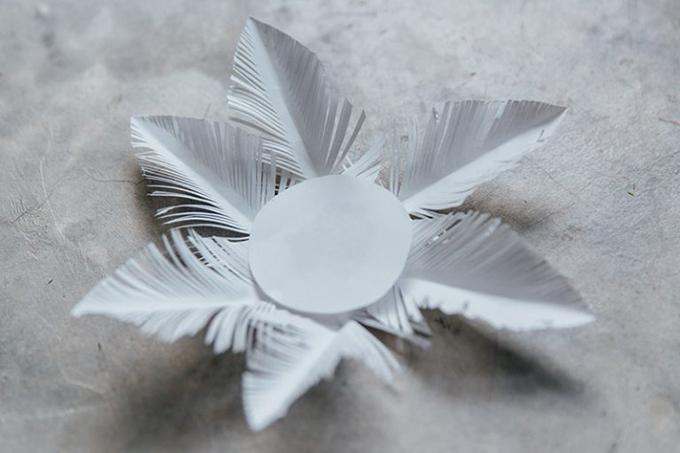 Bước 9: Dùng keo gắn 2 mép của lông vũ vào hình tròn đã cắt từ trước.Làm tương tự với các lông vũ còn lại.
