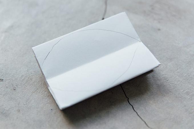 Bước 5: Tiếp tục gấp giấy làm đôi theo chiều dọc và vẽ đường cong ở cả hai bên giấy để tạo thành hình chiếc lá.