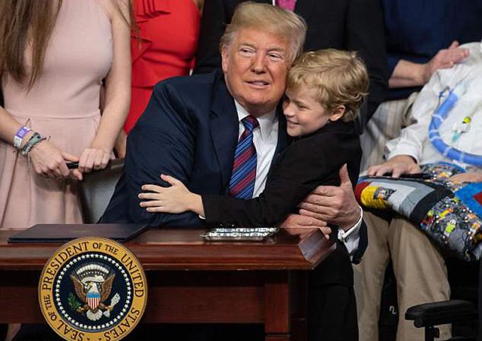 Ông Trump ôm bé Jordan McLinn trước khi khen mái tóc và khuôn mặt cậu bé. Ảnh: AFP.