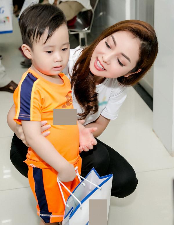 Hoa hậu dỗ dành một cậu bé đang sợ sệt không dám vào khám bệnh.