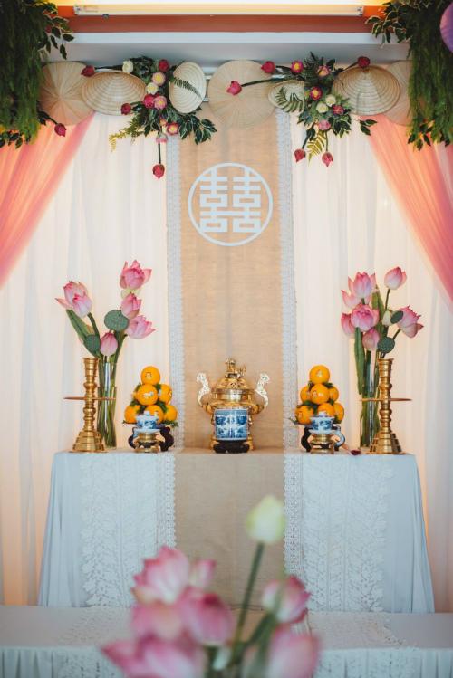 Bàn thờ gia tiên tại nhà gái được sự tô điểm bởi hoa sen. Bên trên trang trí thêm nón lá truyền thống.