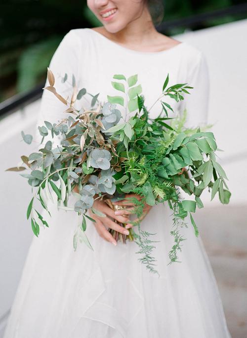 Bó hoa của cô dâu gồm lá dương xỉ, bạch đàn, ô liu và vài cành lá được xịt nhũ vàng lấp lánh.