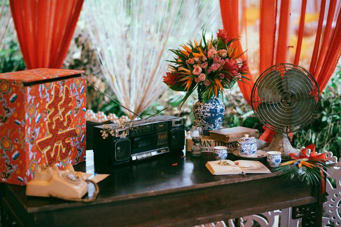Đội ngũ Wedding planner trang trí bàn tiếp tân với đài cassette cổ, điện thoại quay số, đèn dầu, quạt nhỏ và bộ uống trà cổ cùng vài cuốn sách. Trước khi diễn ra hôn lễ, uyên ương cũng không khỏi thấp thỏm lo âu vì những ngày trước đótrời đềuđổ mưa, bão. Cả gia đình đằng trai đều mong trời tiếp tục mưa để sao cho hôm cưới được tạnh ráo. Hôm tôi cưới, trời thương nên ngừng mưa thật. 5h sáng trời còn mưa lác đác vài hạt nhưng lại tạnh và cứ thế đến tận chiều tối, Hữu Anh kể.