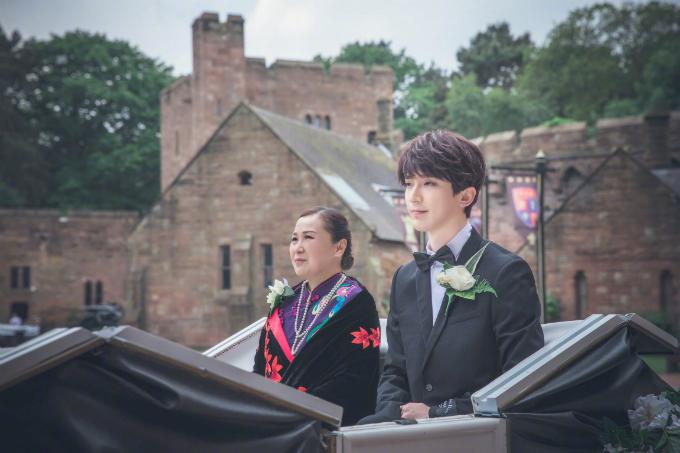 Chú rể cài hoa hồng trắng trên ngực áo và diện vest đen. Mẹ của chú rể cũng có mặt để ủng hộ hôn nhân của con, bà mặc bộ sườn xám tím và cài hoa hồng trắng.