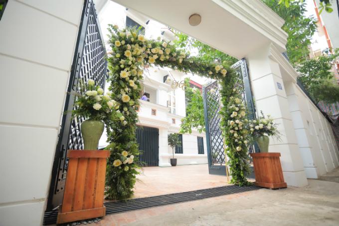 Cổng hoa trước mặt tiền của ngôi nhà được đính kết khá công phu và tỉ mỉ với 2 tông màu chính của lễ ăn hỏi là trắng và xanh lá. Các tàu lá sen xanh, cánh hoa mỏng manh trắng muốt tạo nên nét tinh khôi, mềm mại cho cổng hoa.