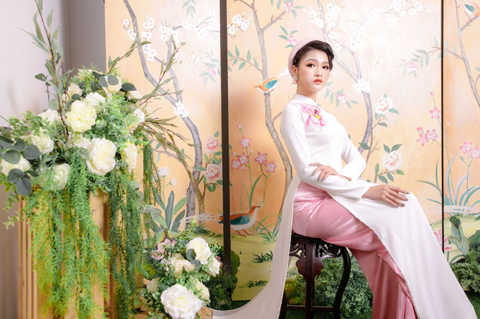 Cô dâu kết hợp áo lụa trắng thêu bông sen to trải dài từ vai áo xuống ngực với quần lụa và mấn hồng nhạt khi muốn làm nổi bật phong cách dịu dàng, nữ tính. Màu sắc các cánh hoa đậm dần vào phía trong là một dụng ý của nhà thiết kế để tạo hiệu ứng thị giác, đem tới nét thanh thoát, nhỏ nhắn cho bờ vai.