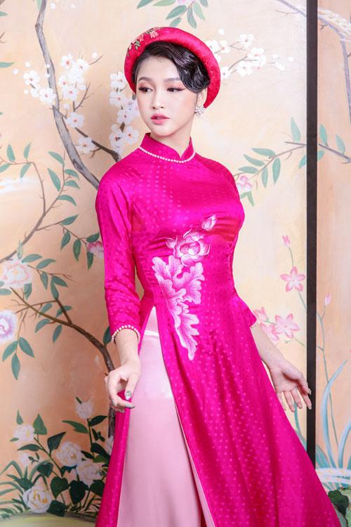 Một nhánh hoa sen thêu màu ombre hồng ngang eo thu hút sự chú ý vào vòng 2 thon gọn.