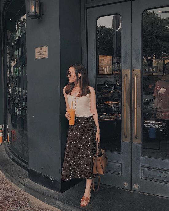 Yến Nhi xuống phố cà phê với thiết kế áo lụa hai dây và chân váy chấm bi. Ca sĩ giúp đôi chân thông thoáng trong ngày hè với dép da đế bệt được sao Việt yêu thích.