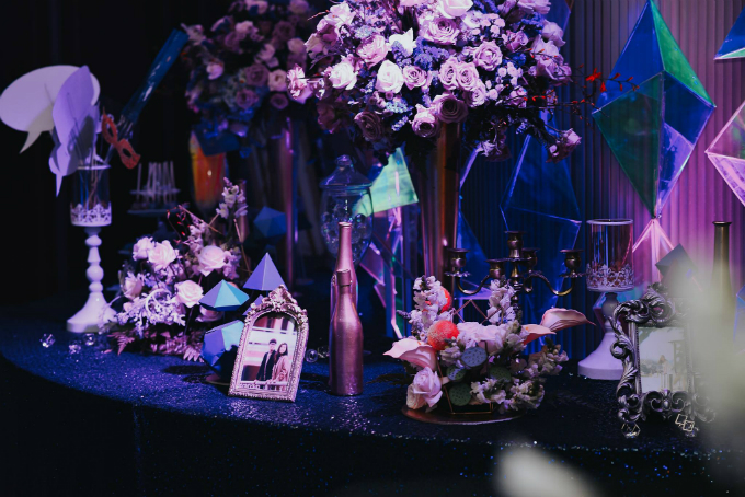 Bàn tiếp tân được trang trí bởi những chai rượu lấp lánh ánh kim, hoa hồng, ảnh cưới của hai vợ chồng và những viên kim cương mô hình. Chiếc bàn được sơntông màu xanh pha ultra violet tuân theo chủ đề vũ trụ của tiệc cưới.