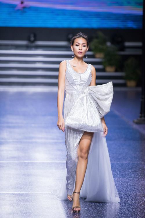 Người mẫu sải bước với chiếc váy lấp lánh ánh kim cổ chữ U tròn và chiếc nơ to bản đính ngang eo. Đồng thời đường xẻ tà từ ngang đùi sẽ giúp cô dâu dễ di chuyển và thu hút ánh nhìn từ người đối diện.