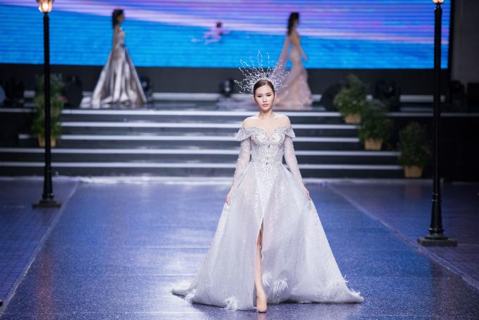 Váy cưới chữ A cách điệucó cổ cúp ngực trễ vai, phần chân váy xẻ tà đượcđính kết lông vũ tạo sự thanh thoát, uyển chuyển trong từng bước đi của cô dâu.