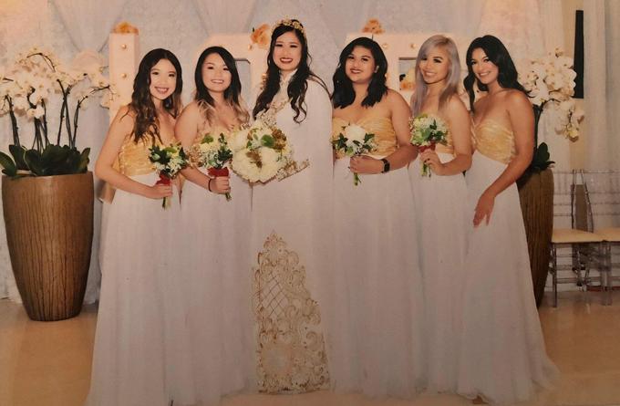 Trang phục của cô dâu và dàn phù dâu đều thống nhất với hai màu trắng - vàng ánh kim.
