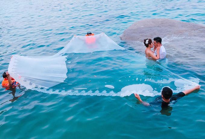 Để chụp cảnh cô dâu - chú rể hôn nhau trên biển, ba cộng sự phải mặc áo phao, dầm nướcđứng xòe váy cưới cho Thu Thảo.