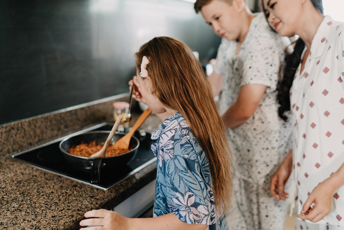 Cô em út nếm thử món sốt bò bằm của anh vừa nấu xong.