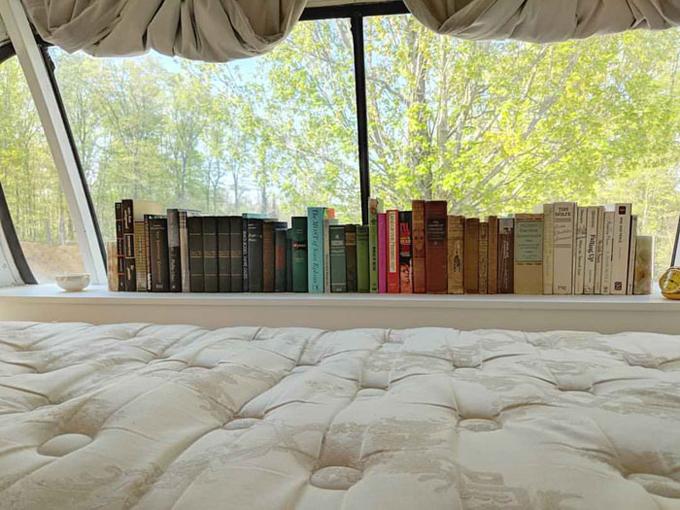 Giá sách đặt ngay cạnh giường ngủ và có cửa kính lớn để chủ nhân tận dụng tối đa ánh sáng mặt trời.