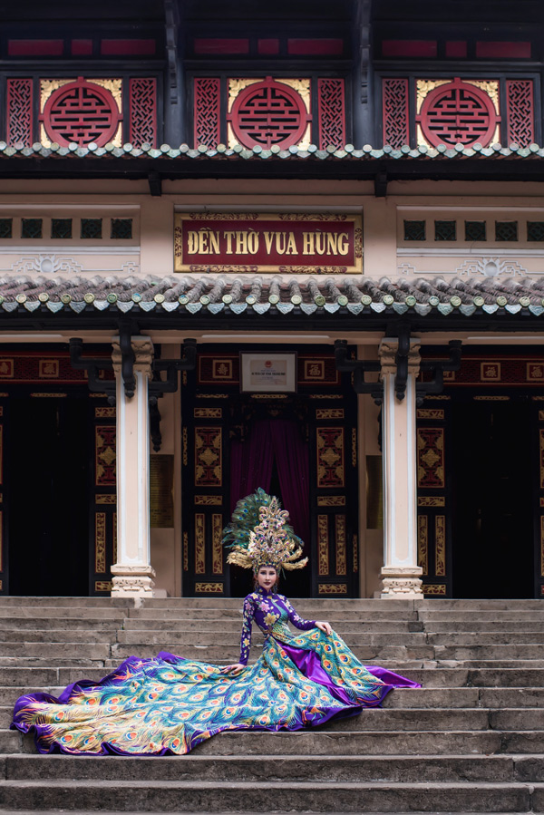 Phần mấn đội đầu đính kết rất cầu kỳ, tà áo dài phía sau cách điệu xòe rộng, họa tiết rực rỡ,giúp Chi Nguyễn hóa thân một nàng chim công xinh đẹp.