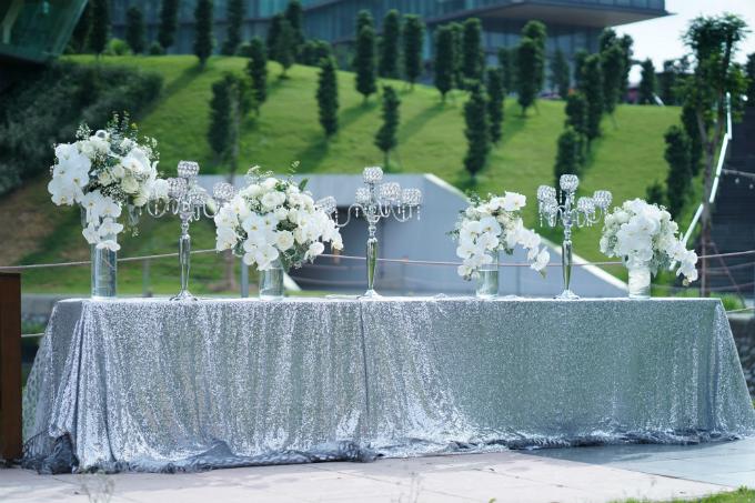 Bàn tiếp tân ngoài trời được trải khăn lấp lánh ánh bạc cùng giá nến gợi cảm giác sang trọng, thời thượng.