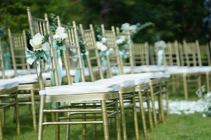 Mỗi chiếc ghế đều được đính thêm vài nhành hoa hồng nhỏ xinh, tăng thêm nét lãng mạn cho không gian làm lễ.
