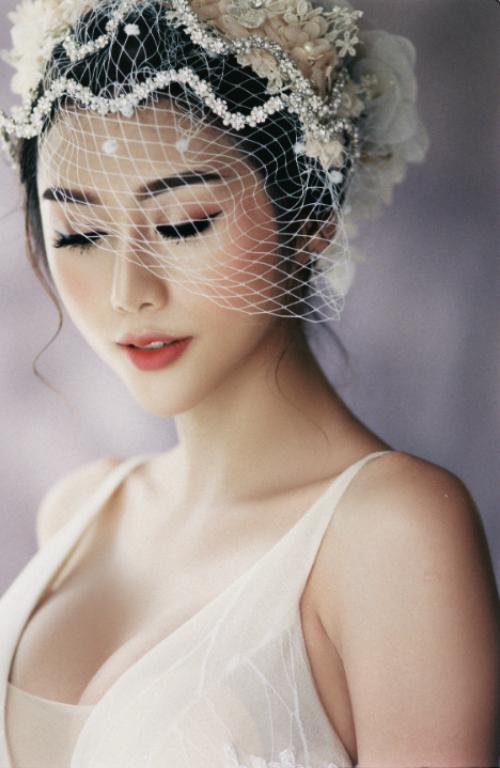 Kiểu tóc búi cao giúp người đối diện tập trung ánh nhìn vào gương mặt của cô dâu. Chuyên gia trang điểm tạo dáng lông mày cong nhẹ, bầu mắt đánh nhũ bạc và hồng đất về phía đuôi. Đồng thời, các bước tạo khối mềm mại với phấn má hồng đất đượctán chéo về thái dương giúp định hình góc cạnh của gương mặt.