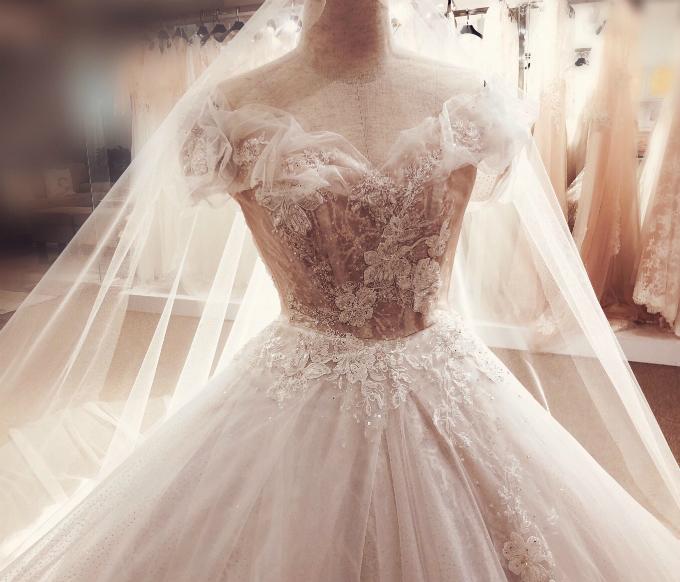 Những hạt pha lê Swarovski được điểm xuyết trên từng cánh hoa, rải rác ở vai và hông, giúp cô dâu thêm lộng lẫy, yêu kiều.