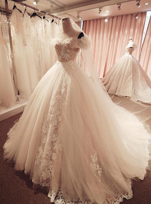 Chiếc váy là một tác phẩm của nhà thiết kế Phương Linh, được may bằng vải ren nhập Pháp. Hoa văn trang trí thân áo không nhiều, nhưng những dải hoa dây leo lúc ẩn lúc hiện giữa các lớp vải mỏng manh tạo hiệu ứng thị giác ấn tượng, độc đáo.