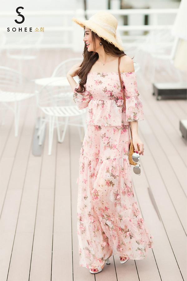 Bộ váy trễ vai màu hồng nhạt với họa tiết hoa in trên nền vải voan là lựa chọncho những cô gái thích phong cáchnữ tính. Thiết kếphù hợp cho chuyến du lịch hècùng gia đình. Trang phục vừa tônnét gợi cảm vừa giúp bạn sành điệu và nổi bật.