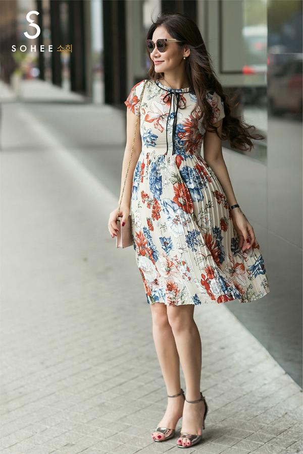 Chị em theo đuổi gu thời trang dịu dàng có thể lựa chọnthiết kế váy hoa xếp ly với phần cổ kín đáo.