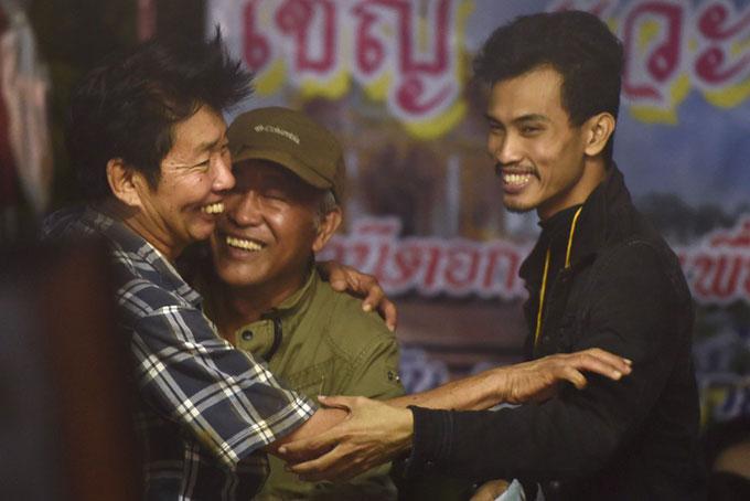 Người nhà của các cầu thủ nhí ôm chầm lấy nhau khi được báo tin 12 thành viên của đội bóng và huấn luyện viên được tìm thấy còn sống. Trước đó, các gia đình cắm trại phía ngoài hang Tham Luang để ngóng tin tức các em nhỏ mất tích sau cơn mưa lớn hôm 23/6. Ảnh: The Nation.