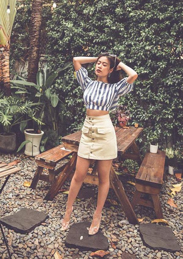 Hoàng Thùy Linh khoe eo thon ý nhị với áo crop top đi cùng chân váy cài nút kiểu lưng cao. Ca sĩ chọn thêm giầy nhựa trong hot trend để phối đồ.