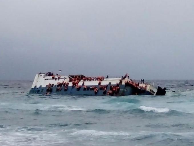 Hành khách bám lấy chiếc phà khi nóbị chìm ngoài khơi đảo Sulawesi. Ảnh:Twitter.