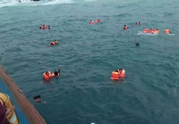 Hành khách mặc áo phao trôi nổi trên biển khơi chờ được cứu. Ảnh: Twitter.
