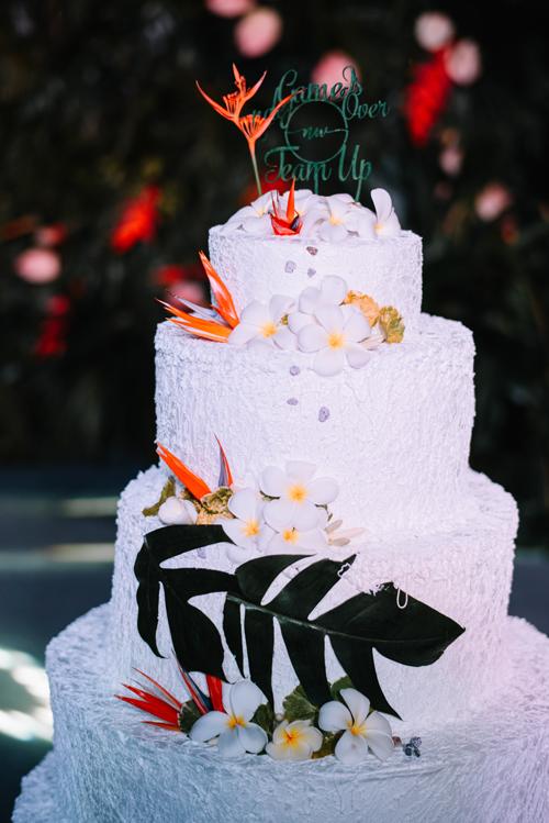 Bánh cưới được trang trí bởi hoa thiên điểu, hoa đại và lá cọ.