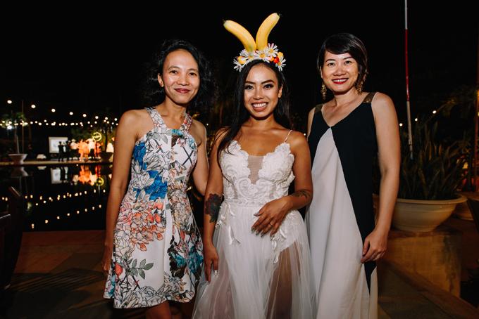 Cô dâu diện bờm chuối và váy hai dây trắng cho hôn lễ bên hồ bơi.