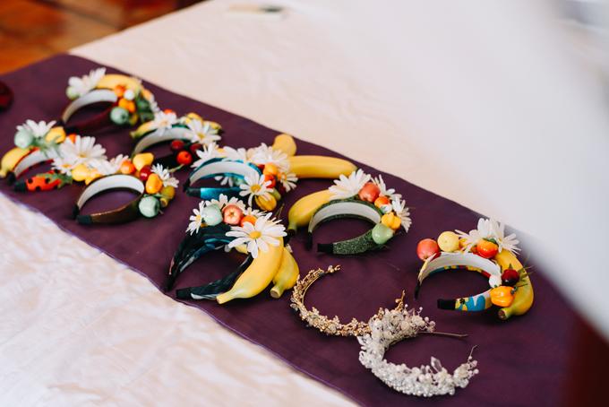 Cận cảnh những chiếc bờm chuối cho phù dâu- món đồ do mộtphù dâu tự lên ý tưởng, tự chuẩn bị hoa giả, chuối giả và thực hiện thủ công. Những chiếc bờm tuân thủ theo bảng màu rừng nhiệt đới của lễ cưới gồm: xanh lá đậm (màu lá chuối), vàng chuối, cam đỏ của hoa thiên điểu.
