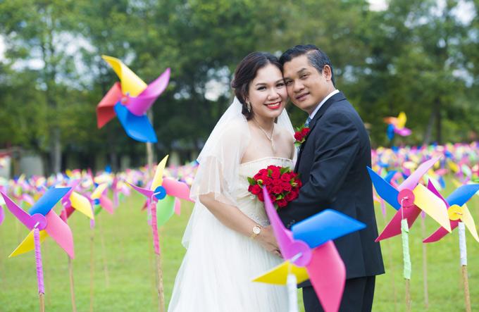Xuân Hiếu và doanh nhân Văn Cường kề vai, áp má giữa cánh đồng chong chóng đầy màu sắc.