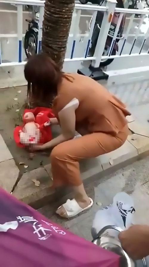 Em bé được người qua đường đặt vào khăn rồi cầm ô che sau khi bị chính bà ngoại mình vứt bỏ. Ảnh: AsiaWire.