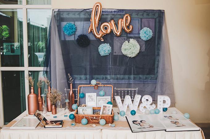 Wedding planner đã trang trí bàn tiếp tân với tên viết tắt của hai vợ chồng, album ảnh cưới, các bóng đèn xanh và những lọ đựng hoađược sơn màu vàng đồng.