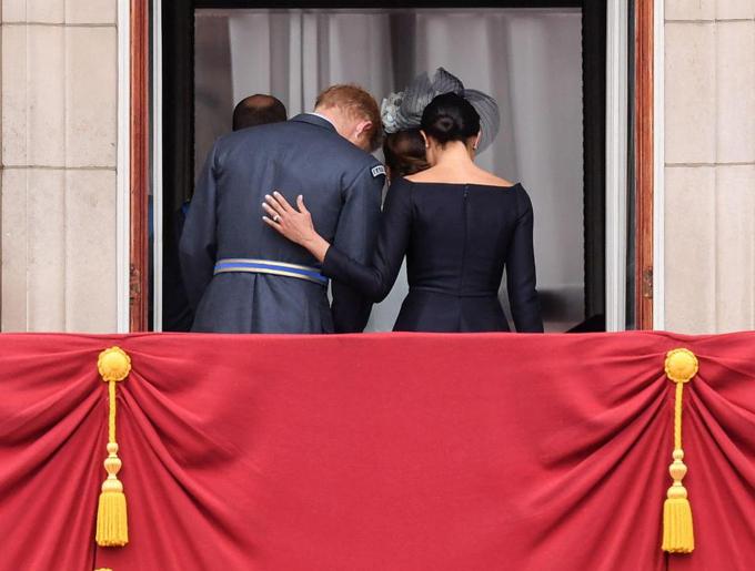 Nữ công tước xứ Sussex đặt tay lên lưng chồng khi rút lui khỏi ban công sau khi màn trình diễn kết thúc.