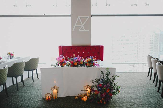Bàn của cặp vợ chồng được tô điểm bởi rất nhiều hoa hồng và nến, ghế ngồi của cả hai mang sắc đỏ thắm nổi bật.