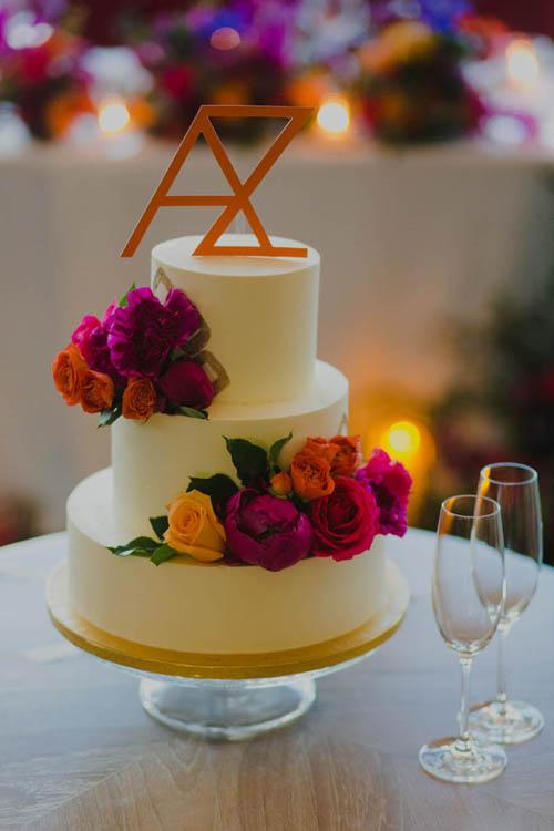 Bánh cưới của Amanda và Zen mang tông trắng và được trang trí bởi chữ cái tên hai vợ chồng và hoa hồng tươi mang sắc đỏ, hồng, cam.