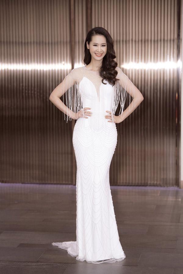 Diện bộ đầm trắng thanh lịch được đínhnhiều ngọc trai cùng chi tiết tua rua ở phần vai, gái một conkhoe trọn được thân hình thon thả.